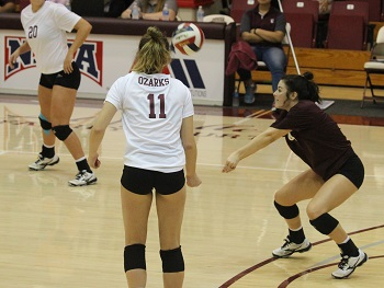 Haley Stallings (dark shirt) hitting the ball with teammates looking on
