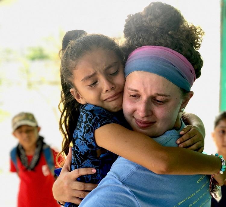 little Belize girl tearfully hugging a player goodbye