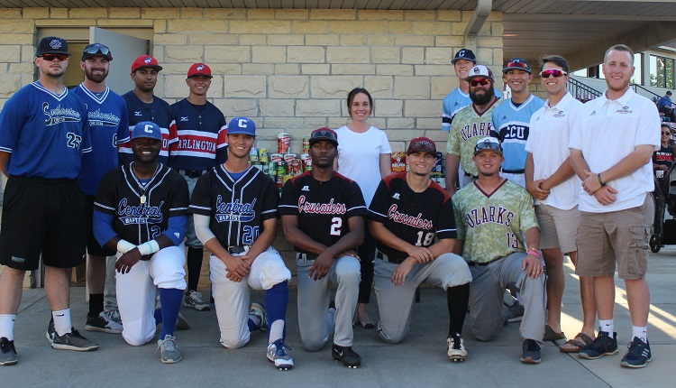 Players posing with Elizabeth Hughes of CAM in front of $700 of canned goods