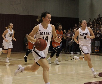 Cass Johnson #14 dribbling down the court against Northern New Mexico College