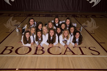 Lady Bobcats frouped on the floor looking up at the camera