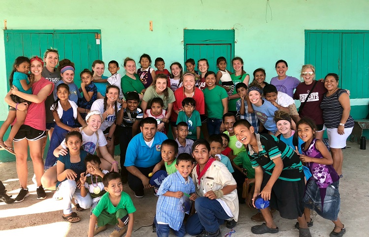 Volleyball team members posing with a group of children from Belize