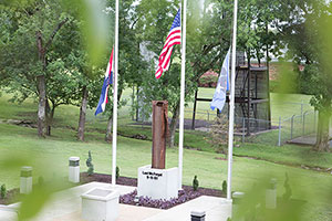 Three flagpoles and a column of metal stand on a stone patio at The Lest We Forget 9/11 Memorial
