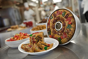 One whole round fruitcake and a plate of fruitcake slices sit on top of a metal table in a kitchen