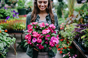 Student in green jacket holding a pot of pink flowers inside a greenhouse
