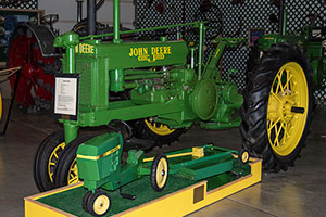 A green, antique John Deere tractor display and a smaller model tractor at The Gaetz Tractor Museum