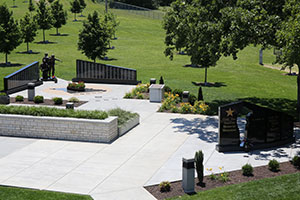 An open air patio space surrounded by trees and stone monuments at Patriots Park near the entrance of the College of the Ozarks