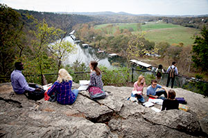 Students sit and study notes on the rocks of Point Lookout over Lake Taneycomo in Branson, MO