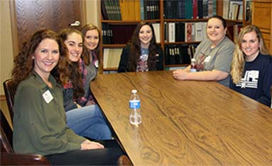 students meet together around table at conference