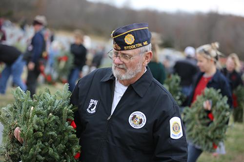 Volunteer Veteran lays wreath at Missouri State Veterans Cemetery.