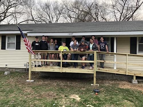 Students and Vietnam Veteran stand on ramp donated by group.