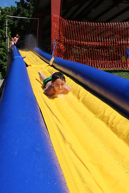 Campers ride the Zoom Floom to cool down with the help of the C of O fire department providing water for the 75 ft inflatable slide at Camp Lookout.