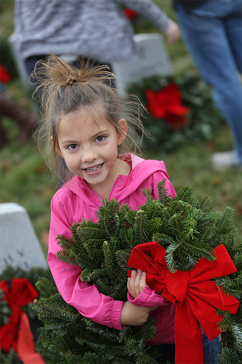S of O first grader, Railey Cizek carries a wreath.