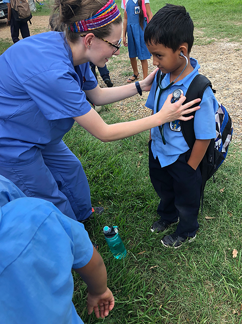 C of O senior nursing student, April Knect, helps a Belizean child listen to his heartbeat.