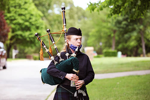 The School of the Ozarks class of 2020 is honored with music by bagpiper Amanda Kershaw, administrators in regalia, signs, and special gifts yesterday, May 7, the originally scheduled date of graduation.