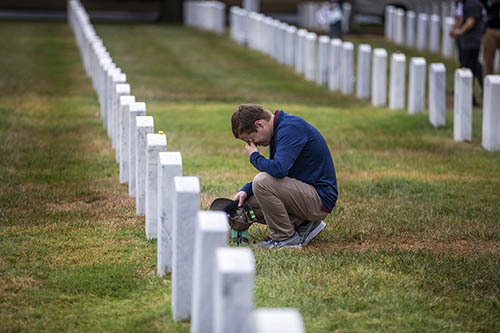Student kneels at tombstone in Arlington National Cemetery.