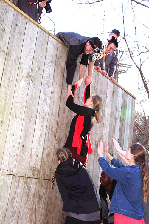 C of O students learn teamwork as they assist their team mates up the wall during Character Camp.