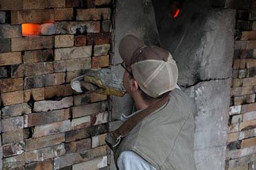 Man checking temperature of kiln