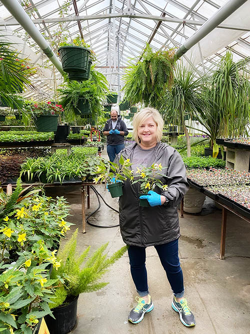 Pamela Spears, administrative assistant and event coordinator for The Keeter Center for Character Education, volunteers to work in landscaping for a day, assisting greenhouse manager Nathan Bell. Normally, more than 15,000 seedlings must be planted each week in order to be ready for spring.