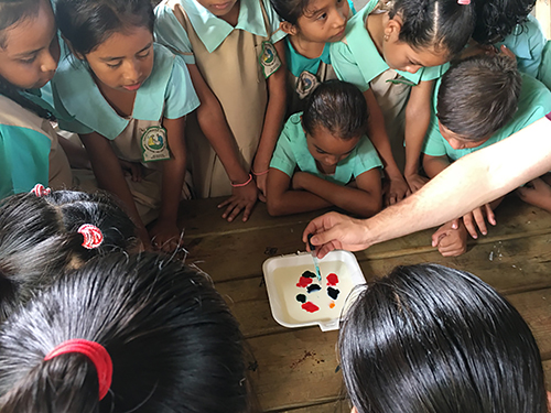 C of O health team does science experiment with children in Belize.