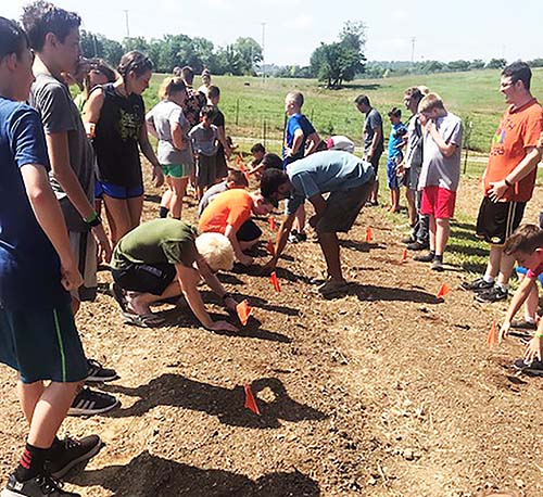 Campers at Camp Lookout help plant pumpkin seeds and learn about gardening.