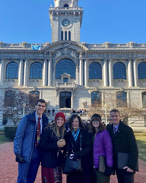 Delegates from C of O stand in front of Mahan Hall at the U.S. Naval Academy in Annapolis, Maryland. (L – R) Senior Gabe Greco; senior Michia Jenkins; Marci Linson, vice president for patriotic activities and dean of admissions; junior Kandice Riley; sophomore Alec Land.