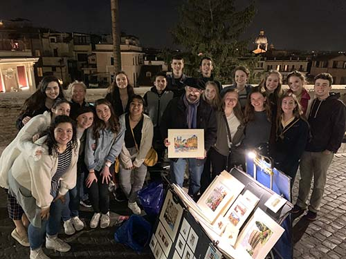 A local street artist visits with students on the Spanish Steps in Rome.