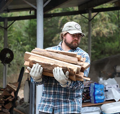 Man carrying wood for kiln