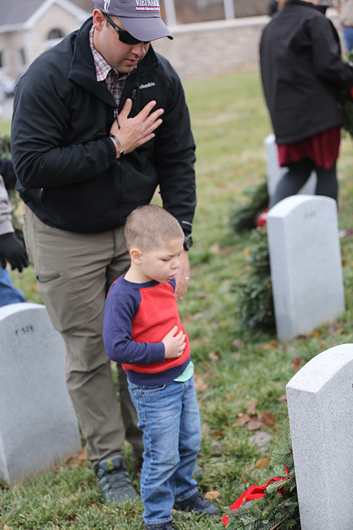 Director of Patriotic Activities and son lays wreath at Veterans Cemetery.