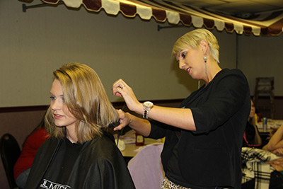 Take One owner Lindsay Eskew cutting C of O student Hannah James' hair