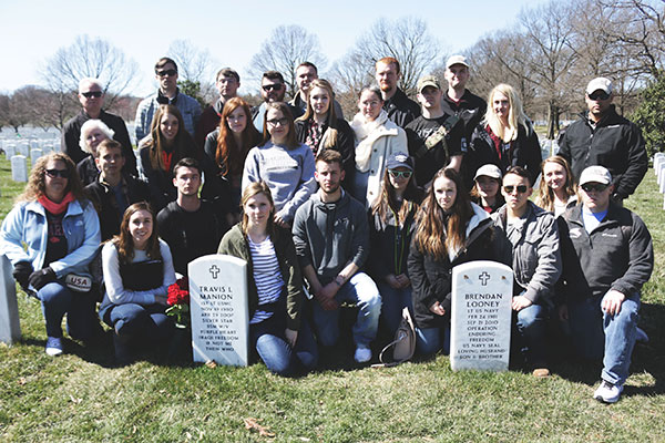 Students and faculty/staff knelled behind tombstones