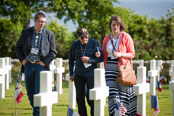 two students with Veteran in military cemetery