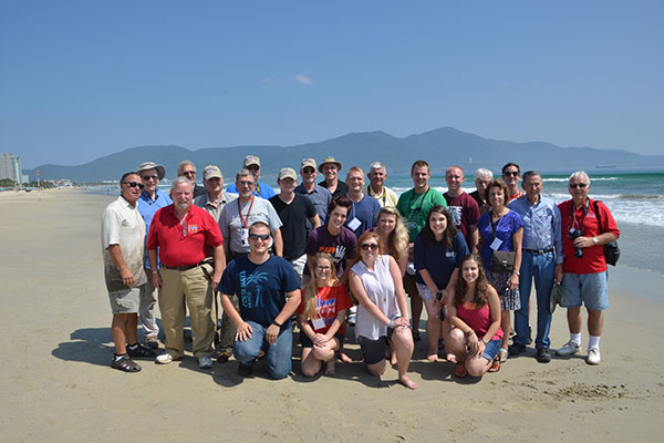 students, faculty and staff on beach with ocean and mountains in background
