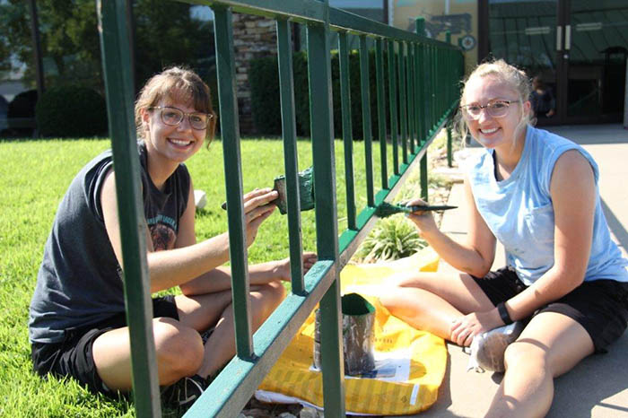 C of O students paint fence during character camp