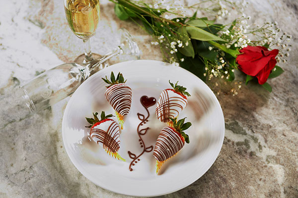Chocolate covered strawberries and heart shaped candies on a plate during the Keeter Center Valentines.