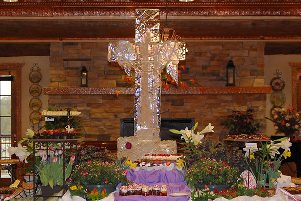 An ice sculpture of a cross with food placed around it during the Easter Brunch event.