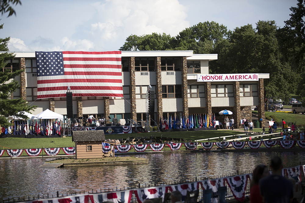 """A stage setup up in front of a building with a sign that says """"Honor America"""" and a giant American flag hanging on the side."""