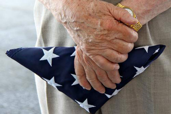 A veteran holding a folded flag.